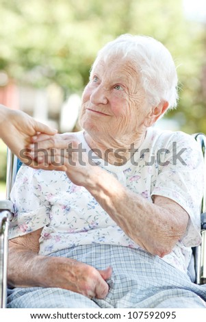 Happy senior woman holding hands with her caretaker - stock photo