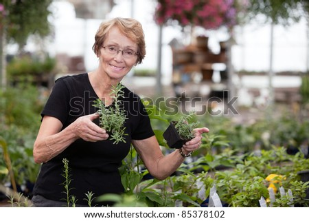 Happy senior woman holding small potted plants