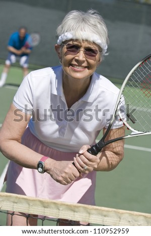 Happy senior woman holding tennis racquet