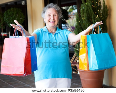 Happy senior woman holds up her arms full of shopping bags.