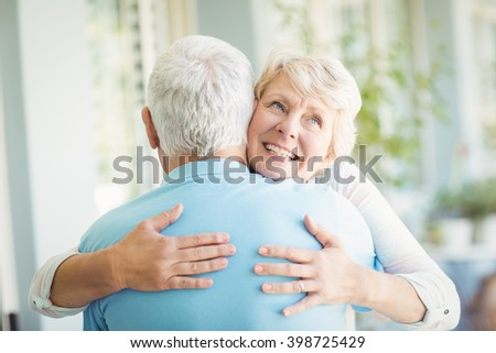 Happy senior woman hugging her husband at home - stock photo