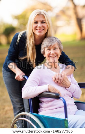 happy senior woman in a wheelchair and her daughter at the park - stock photo