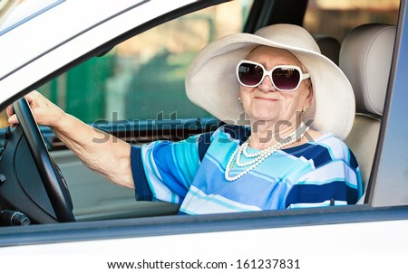 happy senior woman in sunglasses and hat driving automobile . - stock photo