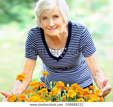 Happy senior woman in the garden,showing orange flowers - stock photo