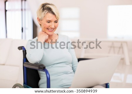 happy senior woman in wheelchair using laptop at home - stock photo
