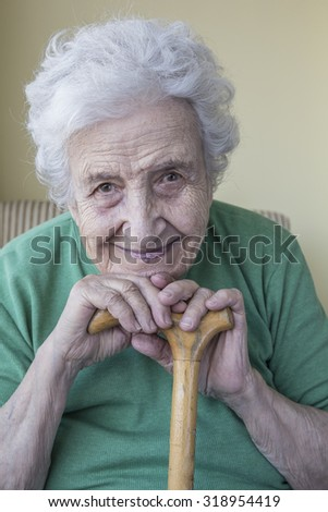 happy senior woman leaning on wooden cane - stock photo