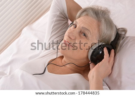 Happy senior woman listen a music in headphones resting in a bedroom - stock photo