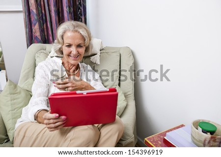 Happy senior woman looking at digital tablet on armchair in house - stock photo