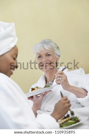 Happy senior woman looking at her friend while eating food - stock photo