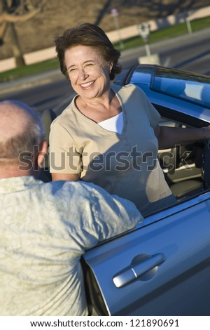 Happy senior woman looking at man while getting down from car - stock photo