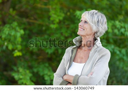 Happy senior woman looking at the beautiful trees - stock photo