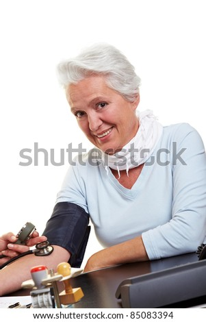 Happy senior woman measuring blood pressure at the doctor - stock photo