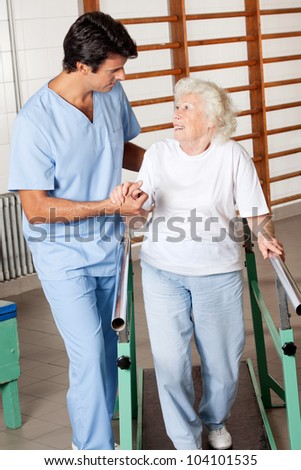Happy senior woman on walking track looking at physical therapist - stock photo