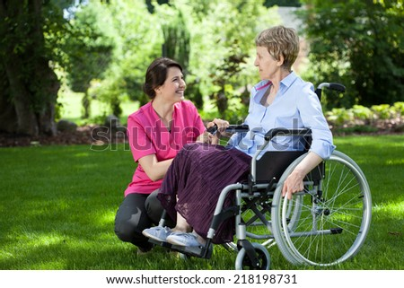 Happy senior woman on wheelchair with caring caregiver outdoors - stock photo