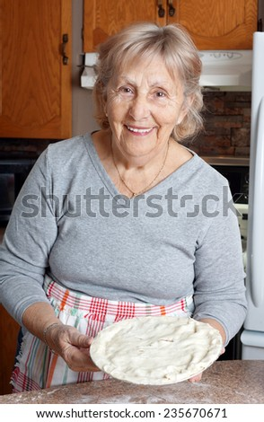 Happy senior woman or grandma showing homemade meat pie in her kitchen - stock photo