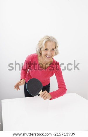 Happy senior woman playing table tennis - stock photo