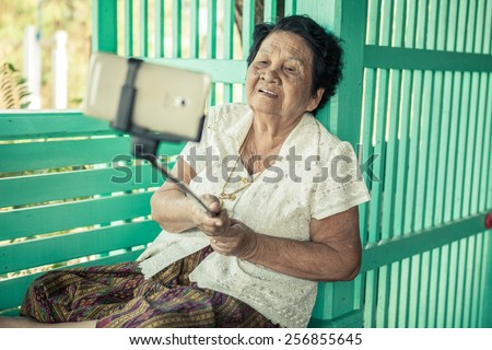 Happy senior woman posing for a selfie - stock photo