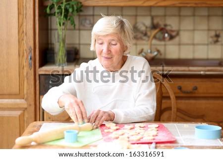 Happy senior woman preparing delicious cookies for her grandchildren - stock photo