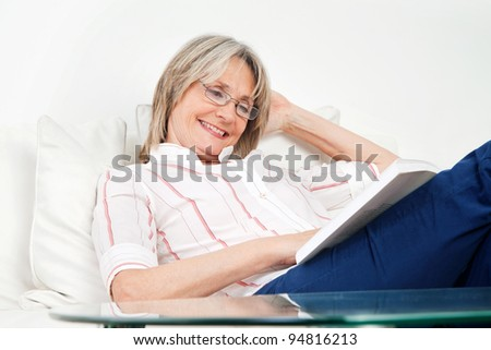 Happy senior woman reading a book on the couch - stock photo