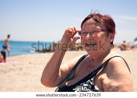 Happy senior woman relaxing on the beach. - stock photo