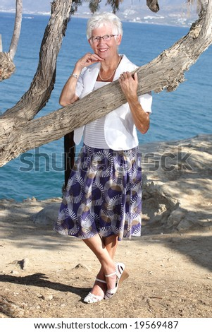 happy senior woman relaxing outdoors - stock photo