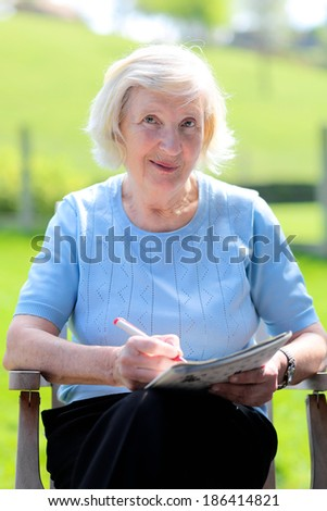 Happy senior woman relaxing outdoors sitting in the garden wooden chair reading newspaper and solving puzzles - stock photo