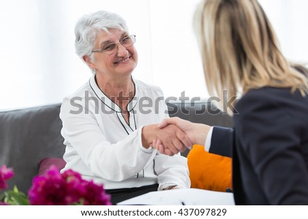 Happy senior woman sealing with an handshake a contract for the retirement