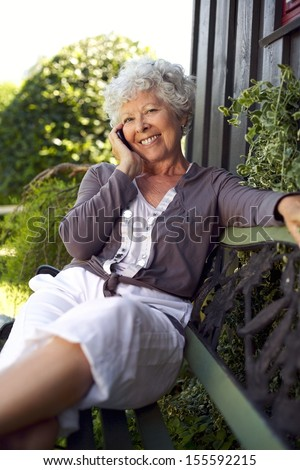 Happy senior woman sitting on a bench in backyard talking on mobile phone and smiling - stock photo
