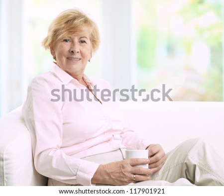 Happy senior woman sitting on a couch while she is drinking a cup of coffee - stock photo