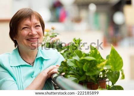 Happy senior woman sitting on balcony and smiling - stock photo