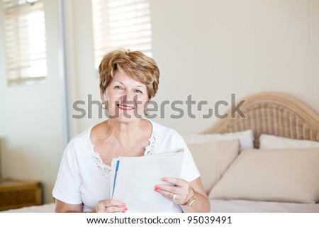 happy senior woman sitting on bed and reading newspaper - stock photo