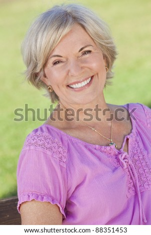 Happy senior woman sitting outside and smiling - stock photo