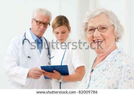 Happy senior woman smiling at camera after her medical exam at hospital - stock photo