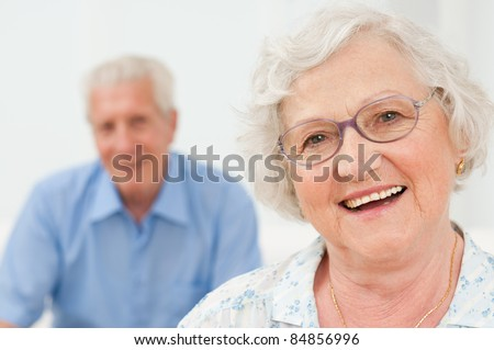 Happy senior woman smiling with her husband on background - stock photo