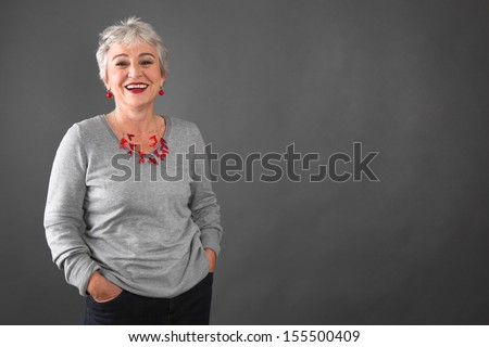 Happy senior woman standing hands in pockets - stock photo