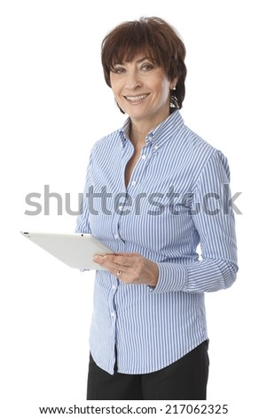 Happy senior woman standing, holding tablet computer, looking at camera. - stock photo