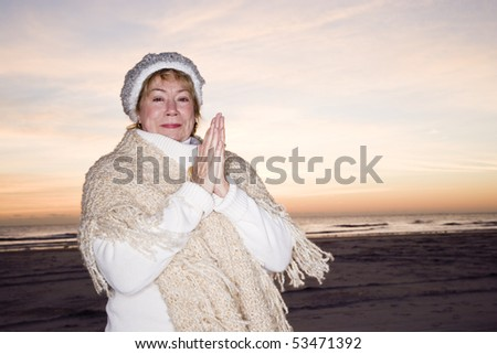 Happy senior woman standing on beach at dawn in winter hat and sweater - stock photo