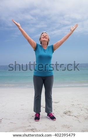 Happy senior woman standing on the beach with hands out stretched - stock photo
