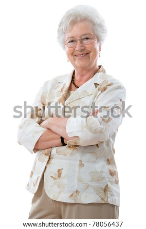 Happy senior woman standing with her arms crossed  and smiling at the camera - stock photo