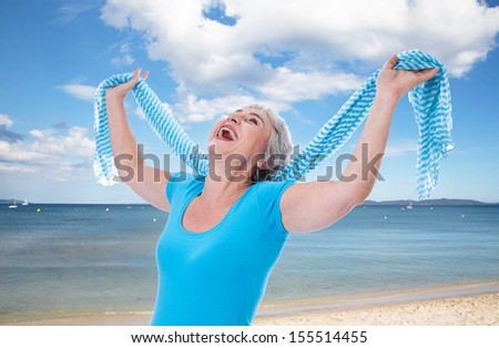 Happy senior woman stretching her hands up on holidays. At the beach in summer times. - stock photo