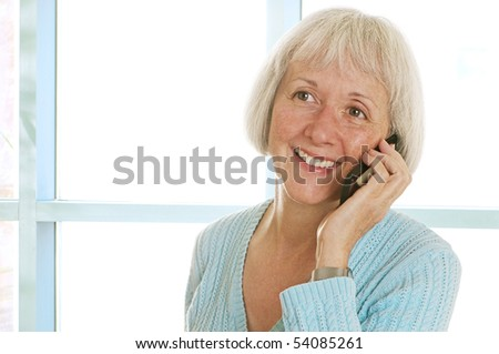 Happy senior woman talking on her cell phone. The image has a slightly soft, glowing look that is by design. - stock photo
