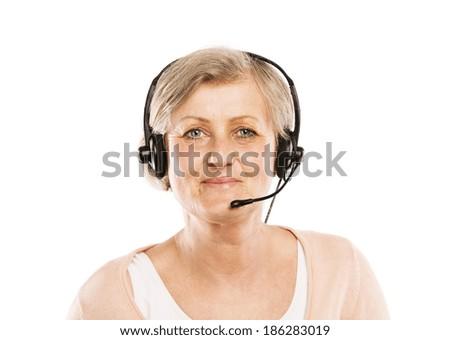 Happy senior woman wearing headset, isolated on white background - stock photo