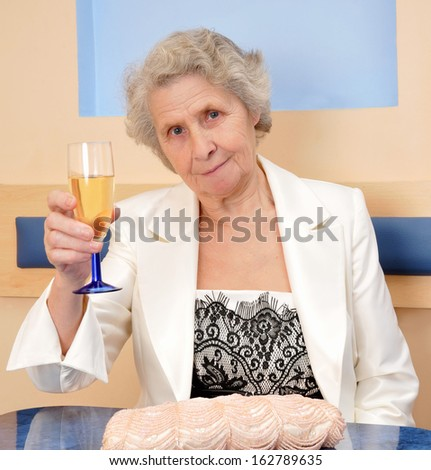 happy senior woman with a glass of wine  - stock photo