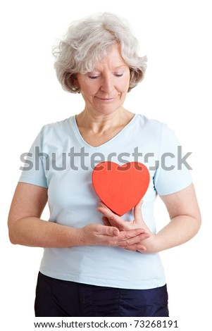 Happy senior woman with a healthy red heart - stock photo