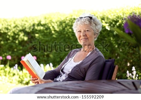 Happy senior woman with book in hand sitting in her backyard looking at camera smiling - Elder woman reading novel in garden - stock photo