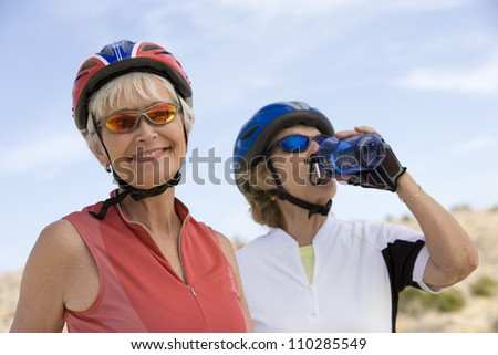 Happy senior woman with friend drinking water