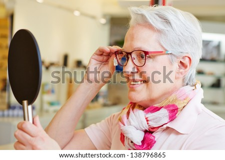 Happy senior woman with new glasses looking in mirror at optician - stock photo