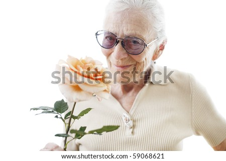 Happy senior woman with rose flower over white background. Close-up, shallow DOF. - stock photo