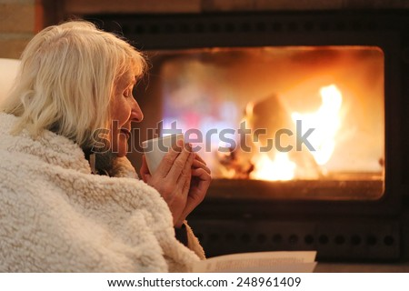 Happy senior woman, wrapped in warm knitted plaid, relaxing at home in the evening, sitting in rocking chair, drinking tea, reading book and enjoying fireplace - successful retirement concept - stock photo