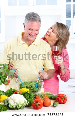 Happy seniors couple cooking at modern kitchen - stock photo